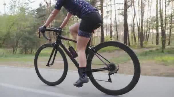 Fiatal női kerékpáros biciklizik a parkban az edzéstervének részeként. Melléklövés..