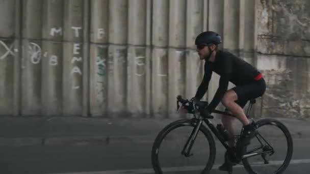 Magabiztos Fit fókuszált kerékpáros lovaglás kerékpáros sisakot visel, fekete ruhában és napszemüveg. Szakállas kerékpár lovas hajtó kerékpár.