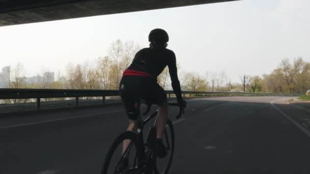 Confident triathlete riding bicycle. Triathlon training. Follow shot of cyclist pedaling on bicycle. Slow motion