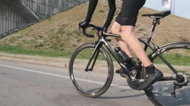 Professional cyclist riding bicycle out of the saddle. Side close up view of leg muscles in motion. Pedaling technique on bicycle. Cycling concept. Slow motion