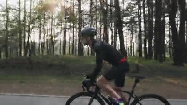 Silný cyklista na kole v parku. Slunce svítí přes stromy. Výstřel z boku. Cyklistická koncepce.