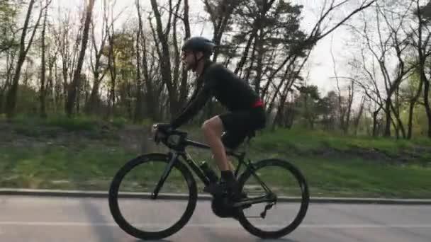 Cyklista nosí černý svetr a šortky jedoucí na černém profesionálním silničním kole v parku. Výstřel z boku. Cyklistický koncept. Zpomaleně
