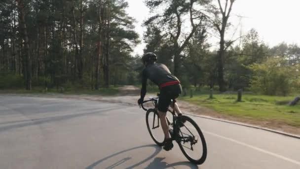 Magabiztos erős triatlonban hajtó a kerékpáros a parkban, mint egy Park az ő képzési ütemtervet a versenyt. Triatlon koncepció. Lassított mozgás