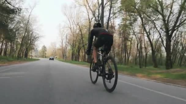 Strong confident triathlete riding bicycle in the park. Back follow shot. Triathlon concept. Slow motion