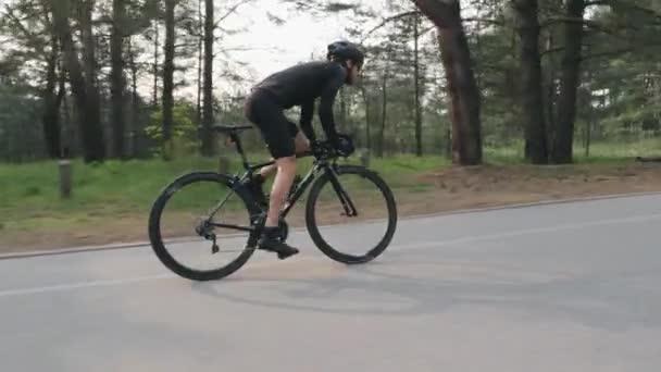 Na kole v parku je silný cyklista. Vysokorychlostní jízda z sedla. Pohled z boku. Cyklistický koncept. Zpomaleně