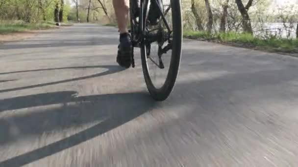 Cyklistický pEdit na kole za zastřelem. Kolo se točí. Silniční cyklistika v městském parku. Zpomaleně