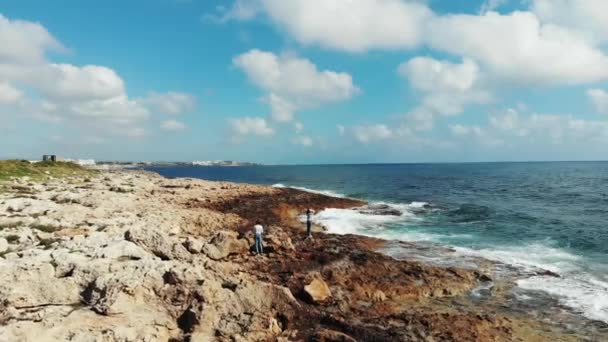 Drone tekintettel a nők képeket fotózásra egy sziklás tengerparton. Erős tenger hullámai ütő sziklák. fotózás a partvidéken