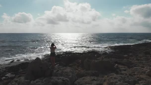 Aerial drone shot woman with phone camera standing on rocky beach taking pictures of sun road and horizon sea ocean. Seashore with female making photos.