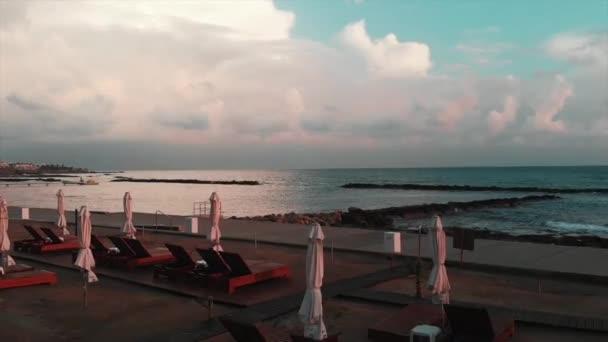 Drohne fliegt durch Strandbereich mit Liegestühlen und Sonnenschirmen mit Meer im Hintergrund