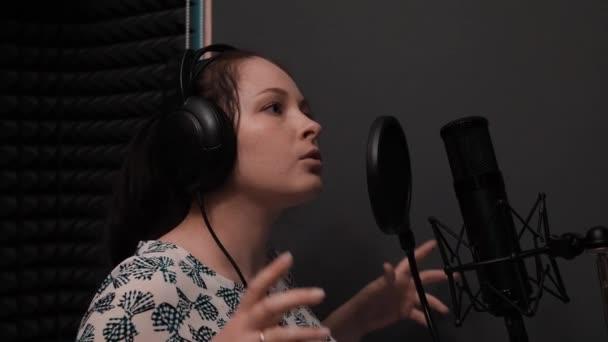 Fiatal lány fejhallgató énekelnek dalt a professzionális mikrofon. Felvétel Hangstúdió
