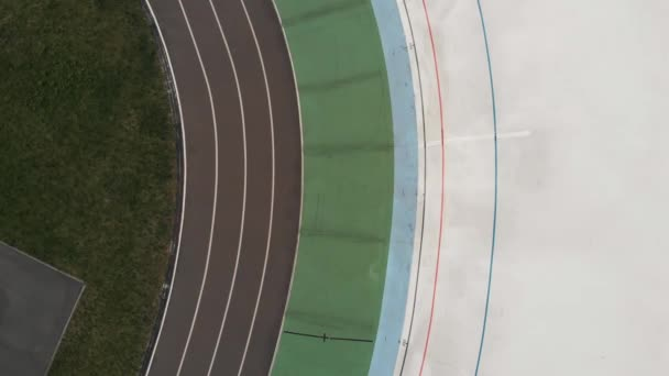 Professional cyclists training at velodrome. Boys on fixed gear bikes riding on cycling track. Cycling concept. Drone top view