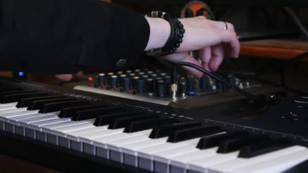 Sound producer engineer pushing and turning knobs and buttons on mixing  board and soundboard in home music recording studio while creating and  producing pop rock music song