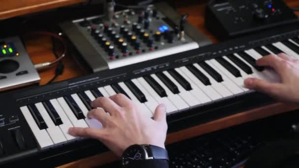Hands playing midi electronic piano while composing pop rock hit song in home recording music studio with mixing board and soundboard. Professional music composer working at home recording music studio.