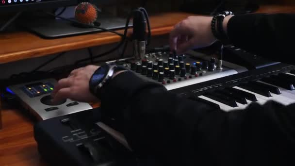 Sound engineer work station with soundboard midi piano and sound engineer mixing board. Hands turning knobs and pushing buttons with equalizer while creating and mixing pop rock music.