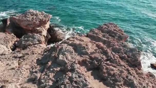 Légi kilátás a sziklás tengerpartról. Gyönyörű tengerpart azúrkék tengervízzel. Óceán hullámai ütő sziklák. Tengeri hullámok fröccsenő és létrehozása hab. Drone lövés az óceán nagy sziklák. Kék kristálytiszta óceáni hullámok