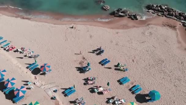 Tourist sandy beach with umbrellas and sunbeds. Family playing on beach. Aerial top view of mediterranean coastline. Beach paradise. Beautiful sandy beach. People resting on beach. Vacation on beach