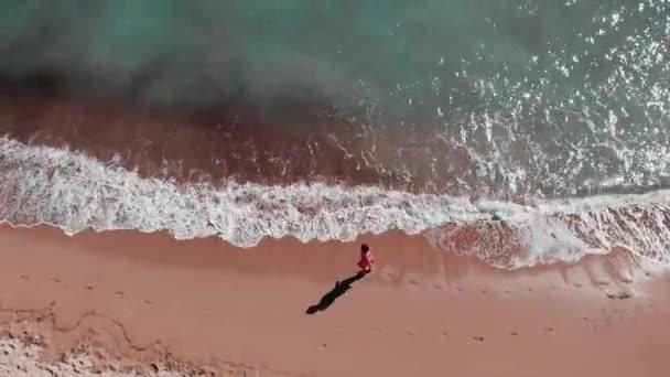 Vonzó nő vesz sétálni a strandon. Fiatal lány sétált homokos tengerparton. A homokos tengerpart légi felsõ nézete. Lány piros ruhában élvező nyaralás és pihentető. Tengeri kék hullámok fröccsenő és létrehozása hab