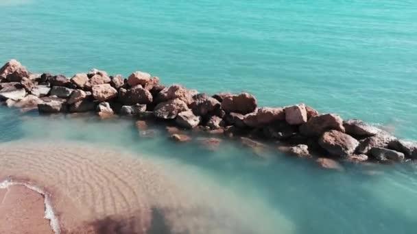 Drone létá písečnou pláží. Letecký pohled na písčitou pláž a modrou čistou mořskou vodu. Nádherná pláž a skalnatý břeh. Drone, výstřelí Středozemního moře. Letecký pohled na mořskou krajinu. Pláž Coral Bay