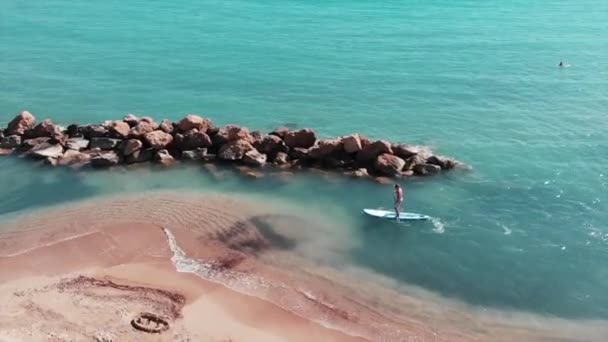 Young attractive man is surfing. Sportive caucasian boy on surfboard. Boy is surfing at seashore. Aerial view of sandy beach with blue clear water. Drone shot of sea blue water