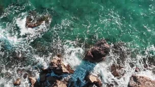 Aerial view of blue clear sea water. Aerial view of sea waves. Blue ocean waves. Waves crashing and hitting rocky stones. Drone shot of cliffs seashore. Ocean waves splashing and creating foam