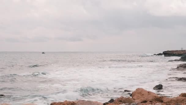 Große Meereswellen stürzen auf felsigen Strand. Schöne Aussicht auf das Mittelmeer mit felsigem Strand. Windig stürmischer Ozean mit großen Wellen. Große stürmische Wellen schwanken ein kleines Fischerboot. zeitlupe