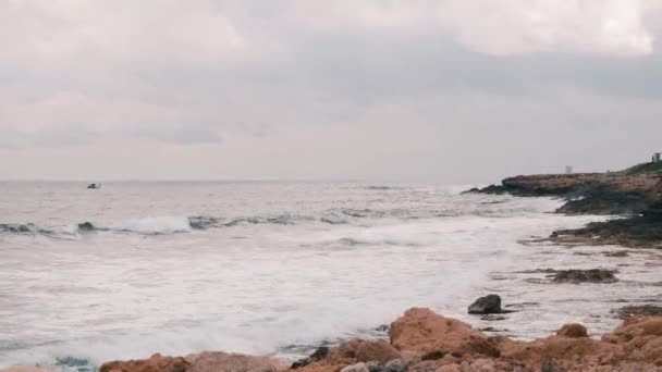 Beautiful big rocky beach of Mediterranean sea. Big ocean waves hitting rocky seacoast. Ocean waves creating foam and splashing. Small fishing boat sailing in open water. White small ship in sea