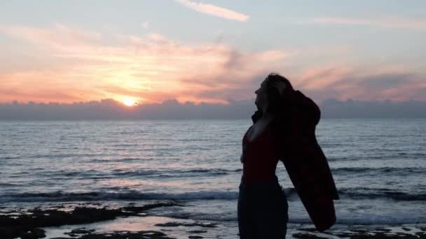 Mladá přitažlivá dívka, otáčející se kolem a usmívající se v kameře. Silueta dívky tančící na pobřeží za soumraku. Horká Kavkazská žena tancuje při západu slunce. Silueta dívky usmívající se na kameru. Zpomaleně