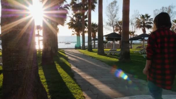 Young caucasian brunette girl in red plaid shirt walking on promenade surrounded by palm trees. Attractive woman walks to quay through hotel beach area. Young girl going to looking at sunset on beach