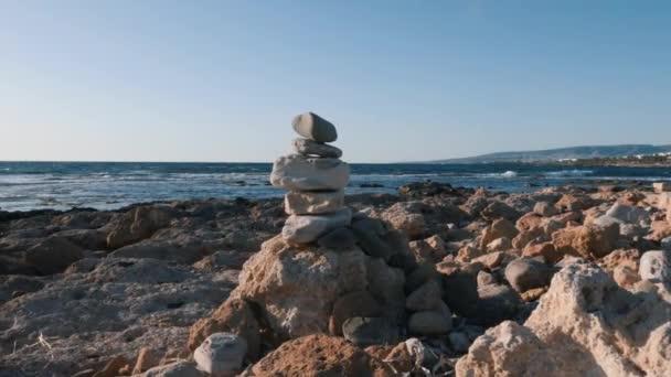 Pyramidy jsou kameny na pláži. Kamenná věž na mořské pláži. Na pláži je blízko hromádky vyrovnaných oblázků. Vyvážené kameny na mořské pláži. Oblázková pyramida na skalnaté pláži