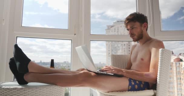Rozrušený mladý opilý chlap ve spodkách a ponožky sedí na balkóně s velkými okny a pití alkoholu při pohledu na monitor