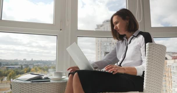 prosperující mladá brunetka byznysmena sedí v moderní kanceláři s velkými okny a pracuje na notebooku, psaní e-mailu a pití kávy