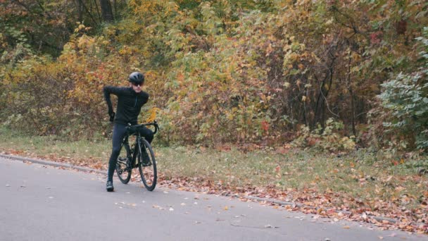 Handsome cyclist starting to ride on road bike in autumn city park. Triathlete pedalling on road bicycle. Male sportive guy in black helmet starting his cycling workout in fall park. Slow motion