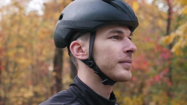 Motivovaný mladý cyklista sportovec v černé helmě nasadí sportovní brýle před tréninkem na kole. Extra zblízka. Cyklistický výcvik v podzimním parku. Jízda na kole. Koncept triatlonu