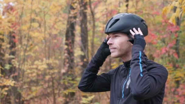 Muž cyklista v podzimním parku. Boční pohled na portrét mladého profesionálního cyklisty nasazuje černou helmu. Cyklistický koncept. Zpomalený pohyb