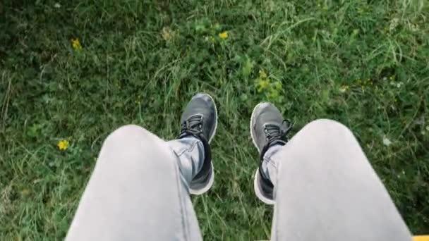 Männliche Füße in schwarzen Turnschuhen am Sessellift über den Pass vor grünem Gras und Blumen, Blick von oben