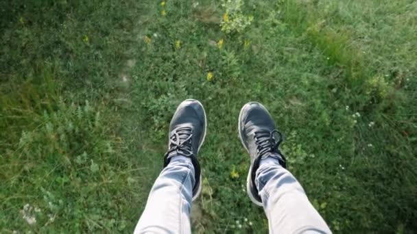 Männerfüße in Jeans und Turnschuhen vor grünem Gras und Blumen in den Bergen, von oben gesehen. Mann sitzt im Sessellift und tritt