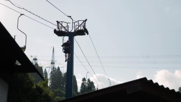 Sedačková lanovka k horskému průsmyku. Muž sedící v dřevěném křesle a šplhající na lanovku na horu. Aktivní dobrodružství