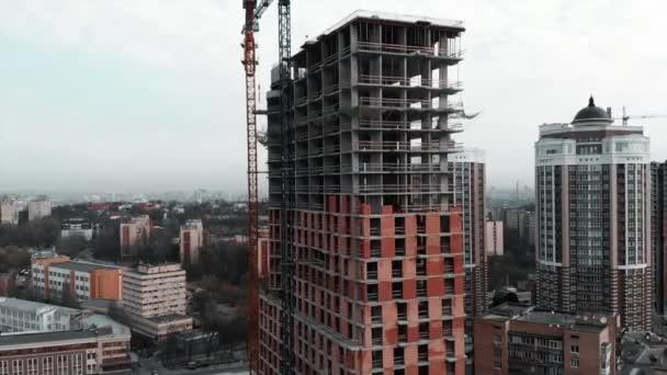 Építődaru az építkezésen. Építése tégla beton lakóépület, légi drón kilátás. Befejezetlen toronyház