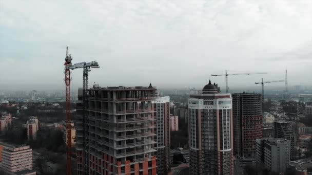 Aerial view of high-rise concrete building construction. Residential complex construction in big metropolis. Drone flying near unfinished brick building