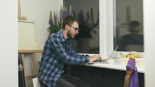Man in glasses and casual wear doing online work tasks on laptop computer on balcony at cozy apartment. Male student studying online, typing on keyboard and preparing scholar project at home