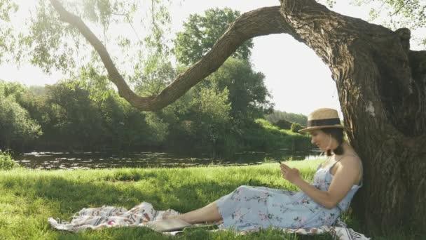 Dívka se opírá o strom v parku a chatuje online s přáteli na sociálních sítích v slunečný letní den. Mladá atraktivní fena v klobouku a šatech sedí na louce v parku u řeky a poslouchá hudbu