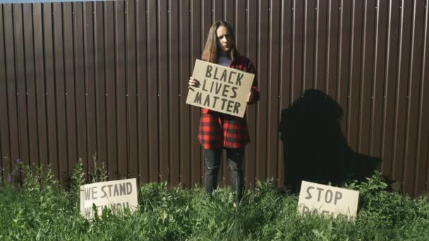 Woman holds sign Black Lives Matter. Caucasian young female holding sign to speak about plurality of violence and anti-Black racism. Poster BLACK LIVES MATTER in hands of woman. Stop Racism concept