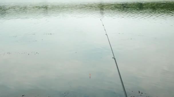 Angelrute im Wasser. Schwimmen Sie auf dem Wasser, angeln Sie mit der Rute auf Wasserreservoirs. Angeln im Freien. Angeln mit Schwimmrute auf dem See. Fische fangen. Mann fischt Fische