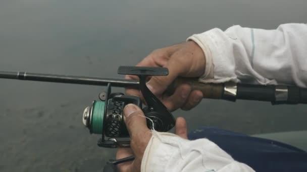 Halászfelszerelést a halászok kezébe. Férfi kezek halászati felszereléssel, halászatra készülve. A halászok életmódjának koncepciója