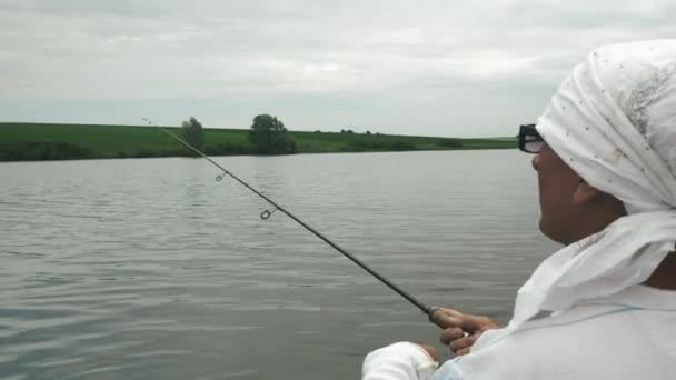A halász halat fog a tavon. Felnőtt férfi halászik a hajón a folyón. Halászat horgászbottal a folyóparton. Ember horgászhal fonórúddal. A halászok életmódjának koncepciója