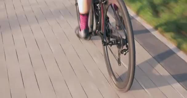 Female cyclist is speeding on road bike in sunshine. Bicycle wheel in motion. Woman is riding road bicycle in park. Bike wheel rotate and spinning. Rear view of cycling gear. Bike chain and cassette