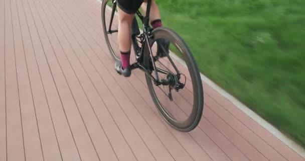 Egy nő biciklizik a parkban. Sportos nő sportruházatban biciklizik a kerékpárúton, nyomkövető lövés. Kerékpáros koncepció. A kerékpáros pedálokat edz és biciklizik. Kerékpáros futómű edzés