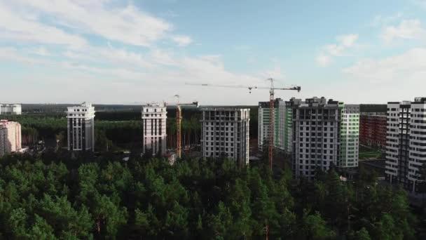 Výstavba moderního módního rezidenčního komplexu obklopeného borovicemi v zeleném lese, letecký výhled