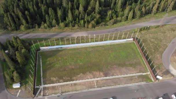 Drone pohled na biatlonové tréninkové tratě s atlety trénink na lyžování mimo sezónu. Speciální sportovní základna v horách v létě, letecký pohled.