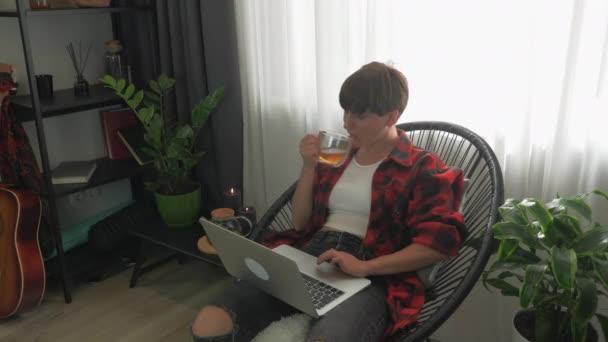 Porträt einer jungen Frau in Freizeitkleidung benutzt Laptop im Homeoffice und trinkt Tee. Weiblich sitzt zu Hause mit offenem Laptop und scrollt Nachrichten online. Studie und Fernarbeits-Konzept